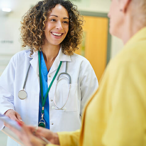 Femail clinicial speaking with mature patient
